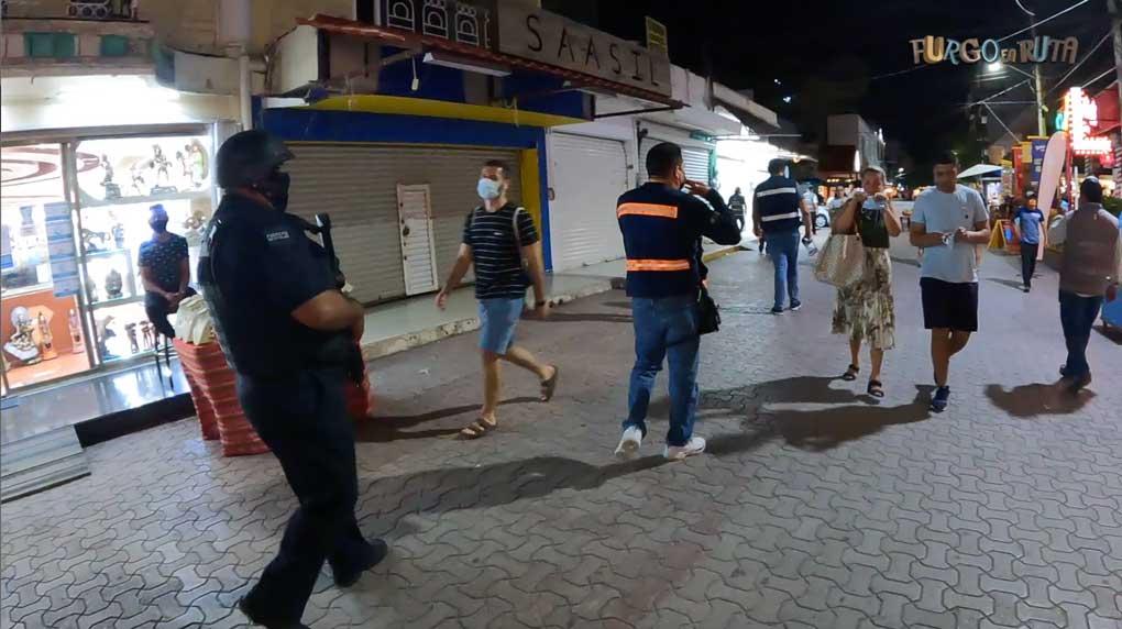 La policía patrulla armada la Quinta avenida de Playa del Carmen mientras dos turistas se ponen la mascarilla a su paso.