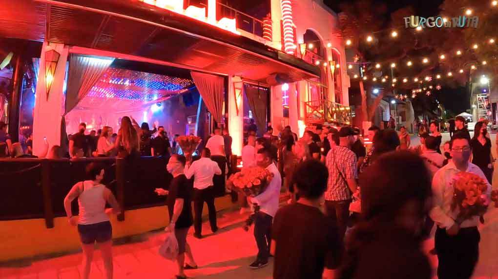 Dos turistas bailan con lo mascarilla puesta en frente de uno de los locales nocturnos de Playa del Carmen.
